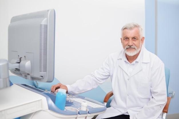 Старший мужчина, сидя на ультразвуковой аппарат в больнице.