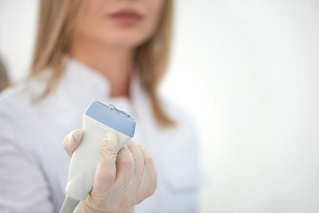 女医の手で超音波検査装置のクローズアップ。