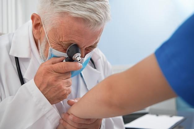 医者は患者の手の皮膚の病気を診断します。