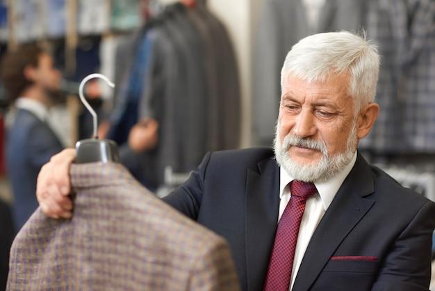 茶色のジャケットを保持しているエレガントな古いクライアントのクローズアップ。