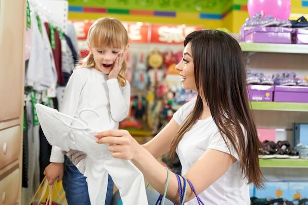 笑顔と大きな店で新しい服を見て女の子