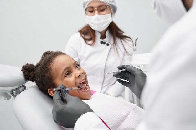 口を開けて歯科医の椅子に横たわっている面白い女の子