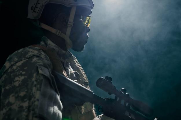 Американский солдат в шлеме и форме стрельба из оружия.