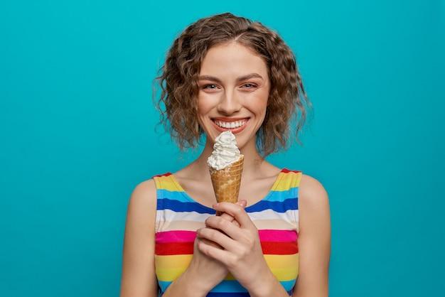 Счастливая девушка в полосатом платье, держа вафельный рожок мороженого.