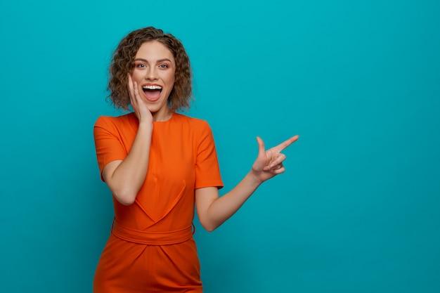Жизнерадостная девушка в оранжевом платье позирует, указывая пальцем.