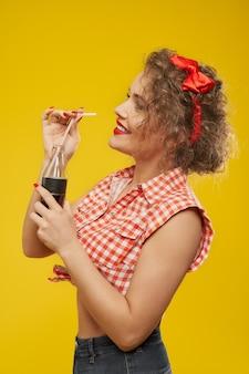 Модель с идеальной прической держит бутылку с напитком.