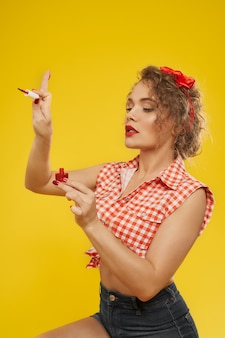 Стильная девушка с красными ногтями маникюр, применяя красный лак.