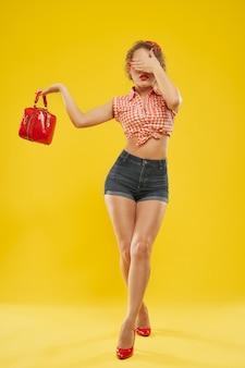 Девушка с красной стильной сумкой позирует с закрытыми глазами.