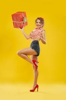 Леди, стоя на одной ноге, держа красный ящик с золотым бантом.