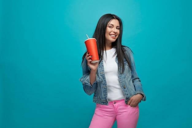 Девушка в стильной одежде, держа красный бумажный стаканчик.