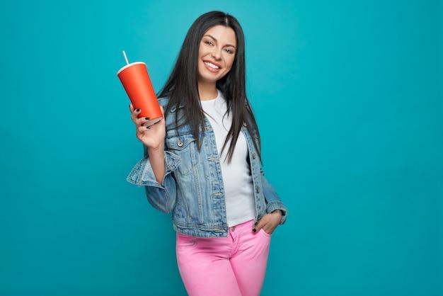 Стильная девушка позирует в модной одежде с красной чашкой.