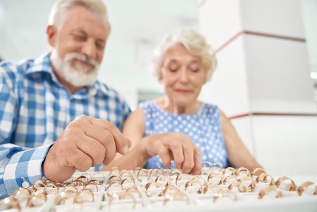 Счастливая зрелая пара покупает новые обручальные кольца в ювелирном магазине