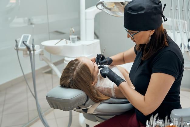 Стоматолог, проверка зубов с помощью инструментов.