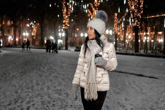 屋外のコーヒーカップとスタイリッシュな冬服の女性。