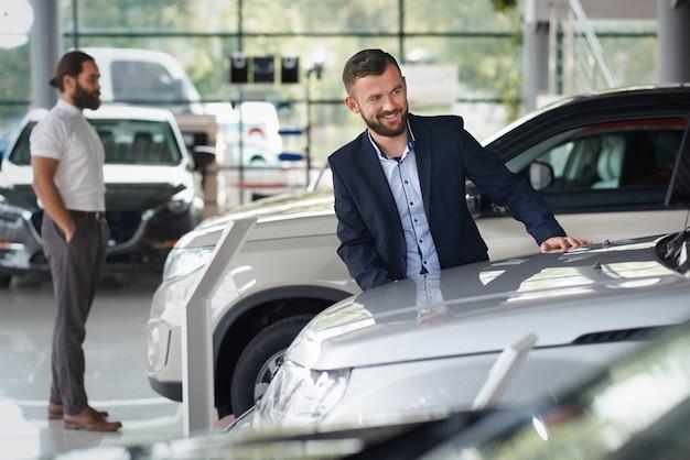 Клиенты стоят в автоцентре и выбирают автомобили.