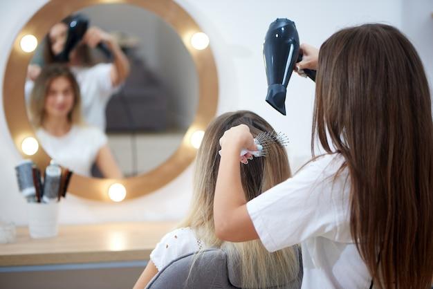 ヘアスタイリング中にヘアドライヤーと櫛を適用する美容師の後ろからの眺め