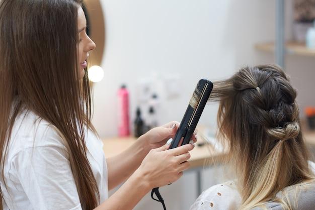 美容院で顧客にカールを行うための矯正を適用する美容院
