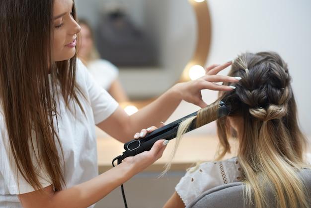美容院で矯正を使用してカールを作る美容師