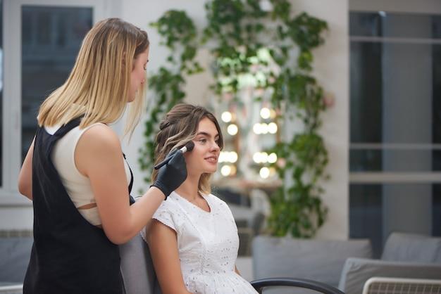 Очаровательная клиентка получает профессиональный макияж в салоне красоты