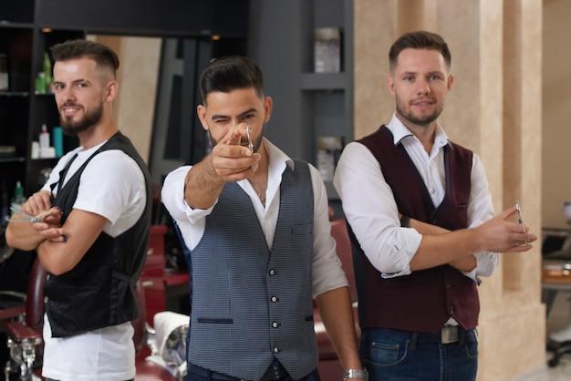 Три мастера позируют с ножницами в парикмахерской.