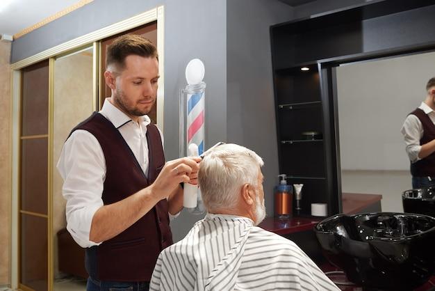 プロの理容室理髪店で男の髪をグルーミングします。
