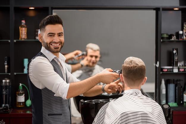 Улыбающийся парикмахер обрезает клиенту стильную стрижку и смотрит в камеру.
