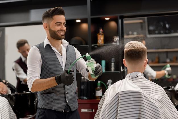 Улыбающийся парикмахер брызгает воду на стрижку клиента с помощью распылителя.