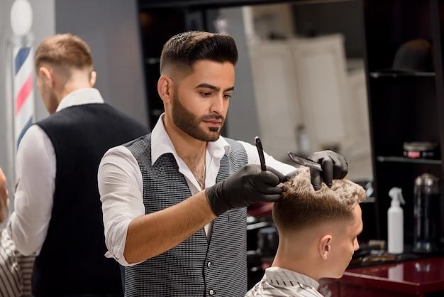 Серьезный парикмахер делает стильную стрижку с помощью расчески и бритвы.
