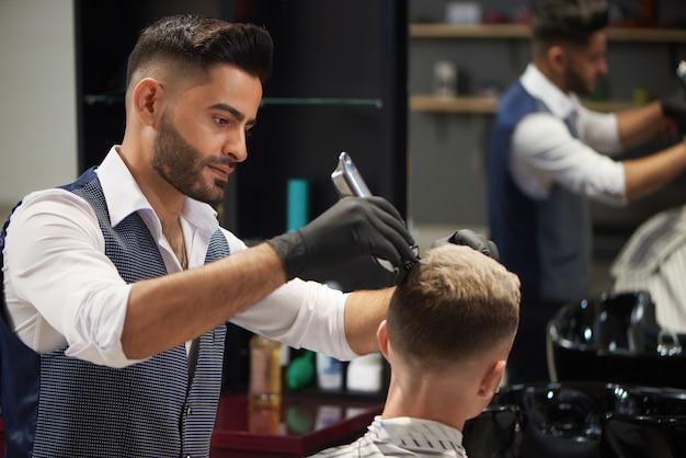 Концентрированный парикмахер подстригает стрижку клиента с помощью триммера.