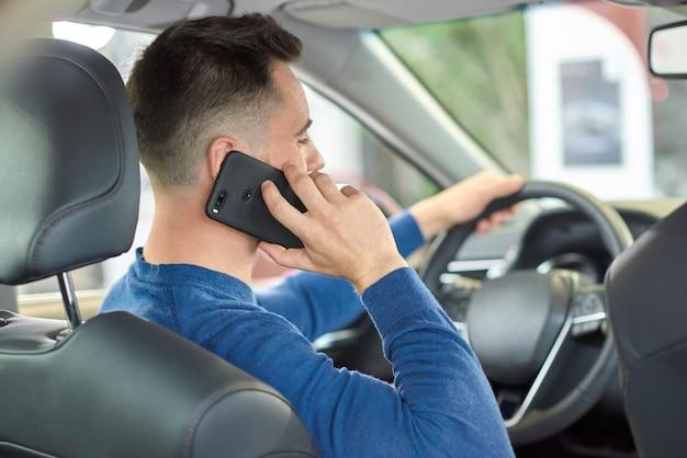 Молодой парень в свитер, говорить через мобильный телефон во время вождения.