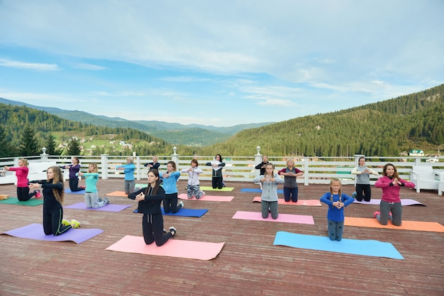 Женщины, стоя на коленях на коврики для йоги, практикующих.