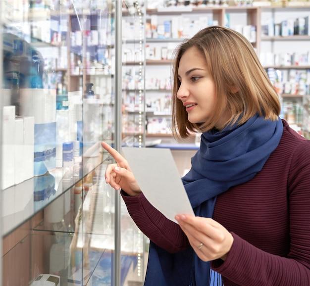Женщина смотрит на полку аптеки с медицинской продукции.