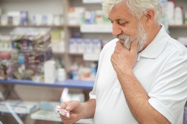 Пожилой мужчина мышления, держа таблетки в аптеке.