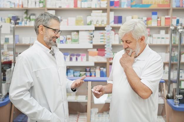 Консультация пенсионера и фармацевта в аптеке.