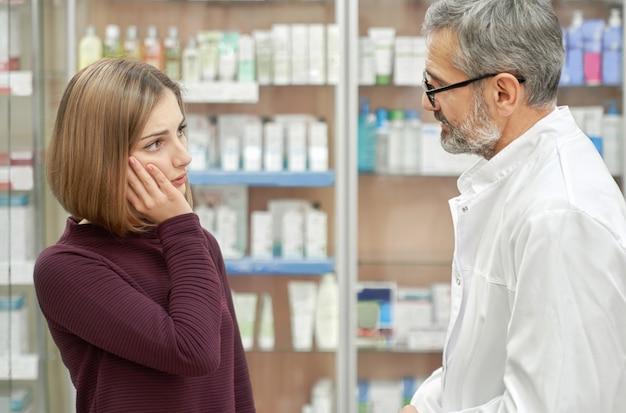 Аптекарь помогает женщине с зубной болью.