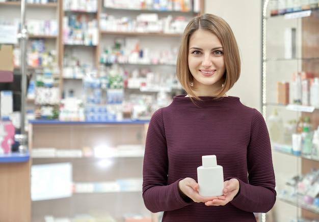 Женщина позирует в аптеке с белой косметической бутылкой.