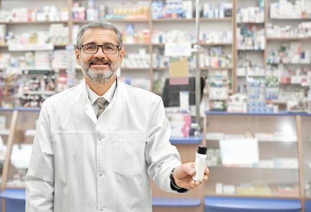 Аптекарь в белом халате улыбается, позирует в аптеке.