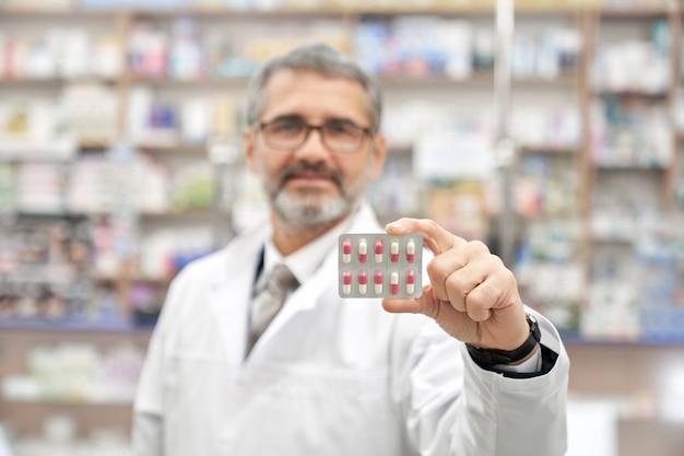 Химик холдинг блистерной упаковки с таблетками.