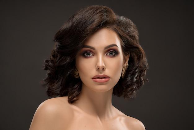 Элегантная гламурная модель со стильным макияжем и прической