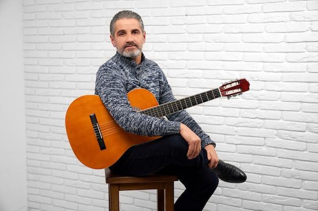 ギターとスタジオでポーズをとる中年の男性。