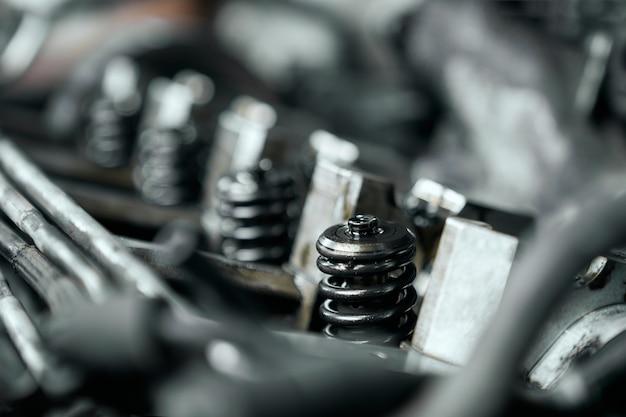 開いたボンネットの下で車のエンジンのノズルのクローズアップ