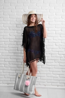 Молодая женщина носит черное парео и шляпу с сумкой