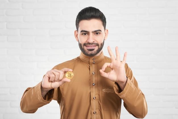 Молодой арабский человек держит биткойны