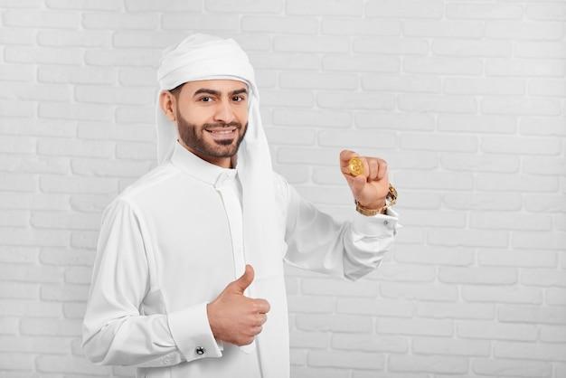 笑顔のアラビア人がビットコインを保持