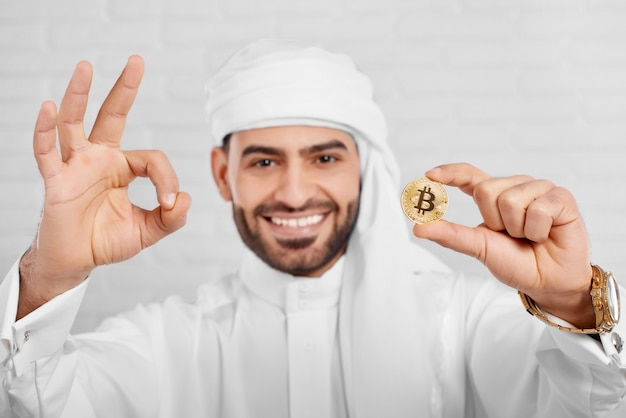 笑顔のイスラム教徒の男性の肖像画はビットコインを保持します