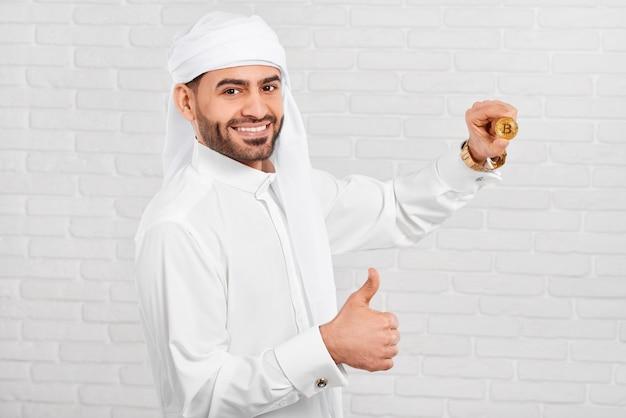 笑顔のアラビアのビジネスマンはビットコインを保持します