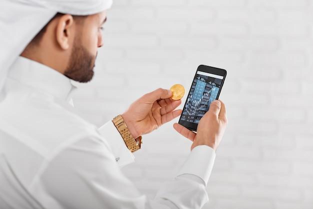 若いイスラム教徒のトレーダーは黄金のビットコインと携帯電話を保持しています