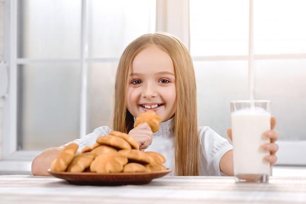 Милая маленькая девочка ест печенье с молоком и улыбается