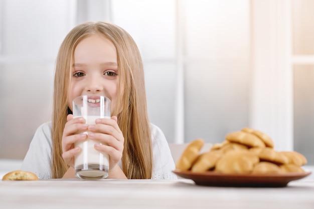 Маленькая девочка со светлыми волосами пьет стакан с молоком