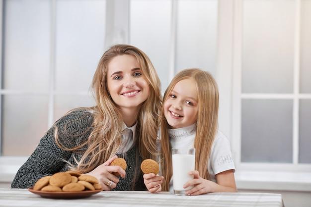 Старшие и младшие сестры едят печенье и улыбаются